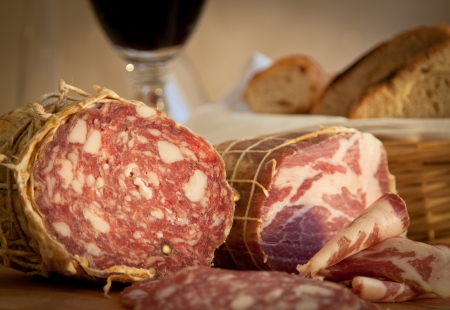 salame: Close-up on delicious Italian salame and capocollo  Bread and wine in the background  Landscape orientation
