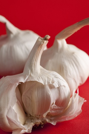Half garlic clove on red background and whole cloves on the back Stock Photo - 13874649