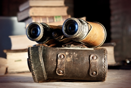 Vintage binoculars and their case, with travel books in the background