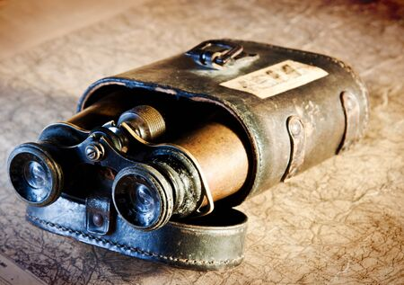 antique binoculars: Detail of vintage binoculars in their case, resting on an old map