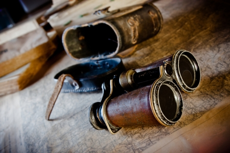 antique binoculars: Old binoculars on an old map  an explorer planning the next expedition