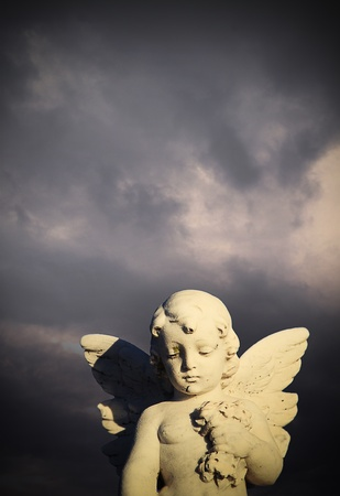 Anel statue in cemetery against a stormy sky photo