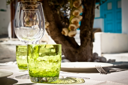 dinnerware: Table setting for al fresco dining in a picturesque village street with olive tree and garlic in the background  Stock Photo