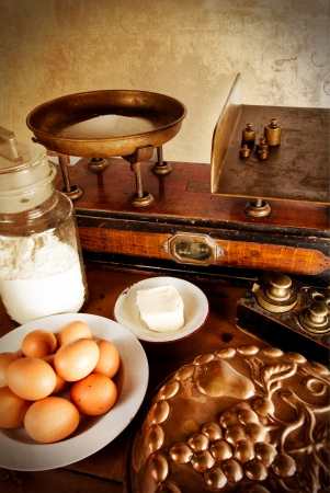 kitchen scale: Vintage scales with all ingredients for a good cake  eggs, flour, sugar, butter and a beautiful old copper cake tin