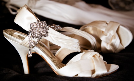 Wedding shoes on the bed with wedding gown in bckground  Focus on the jewels  photo