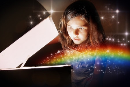A little girl opening a magic chest and setting the rainbow free amongst glittering stars. Christmas or birthday concept the magic of gifts.