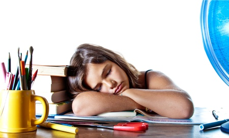 Little girl falls asleep on her homework. Isolated on white background with plenty of copyspace.  photo