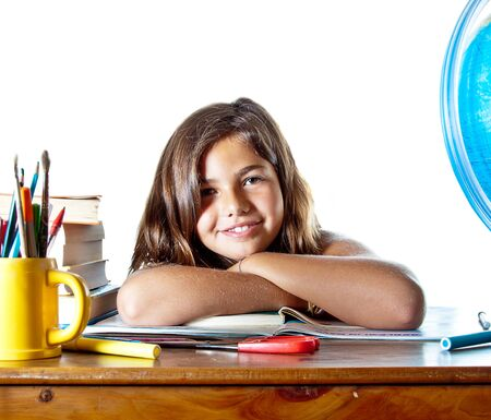 Little girl wakes up after sleeping on her homework. Isolated on white background with plenty of copyspace. Stock Photo