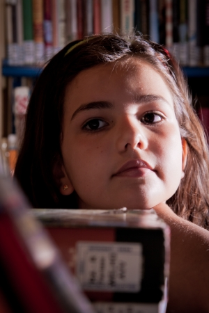 A little girl looking for a book in the library shelves Stock Photo - 14043391