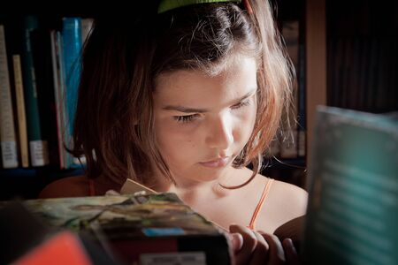 boffin: A little girl reading in a library, completely absorbed in her book, seen through the bookshelves.