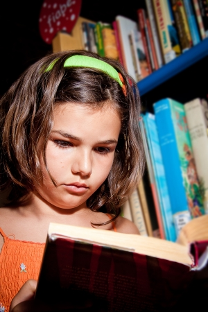 bookish: A little girl reading in a library, completely absorbed in her book senn from below  Portrait orientation