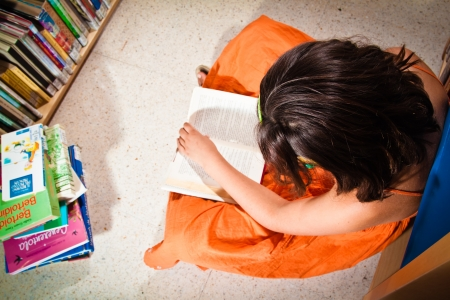 boffin: A little girl reading in a library sitting on the floor, completely absorbed in her book, seen from above   Stock Photo