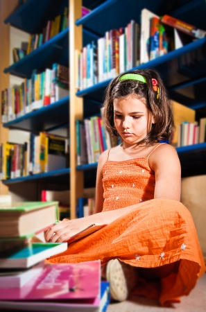 A little girl reading in a library sitting on the floor, completely absorbed in her book, seen from below  Portrait orientation