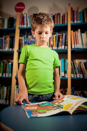 absorbed: Little boy absorbed in a book in a public library