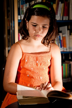 A little girl reading in a library, completely absorbed in her book  Stock Photo - 13897930
