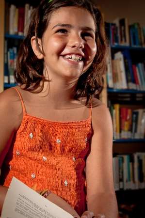 A little girl reading in a library, taking some time off to laugh  Stock Photo - 13897847