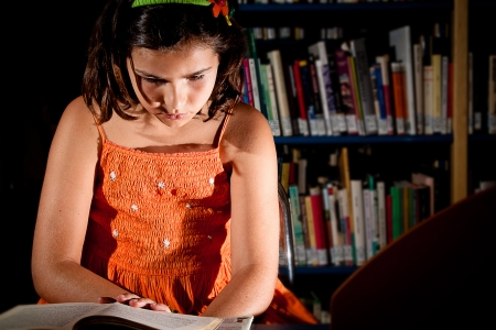 bookish: A little girl reading in a library, completely absorbed in her book  Portrait orientation