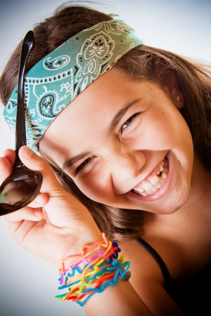 Young girl laughing her head off, wearing bandanna and colourful bracelets  photo