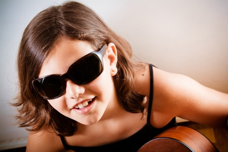 Pre-teen girl playing acoustic guitar wearing sunglasses  photo