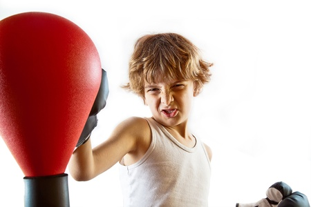 boy boxing: Cute kid training with punching ball and making the appropriate faces  Plenty of copyspace