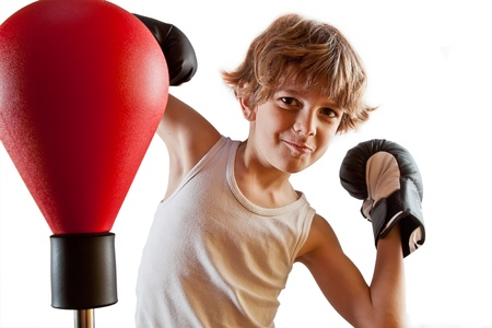 muscle boy: Kid with attitude during boxing training with punching ball  Stock Photo