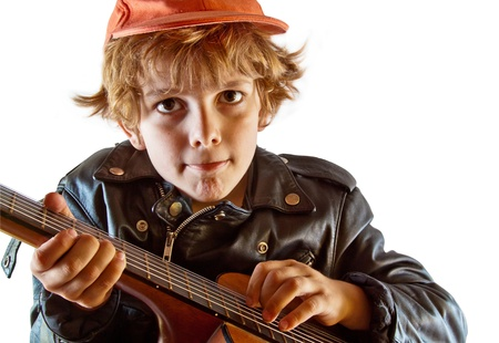 Cute small kid learning to play guitar with great concentration