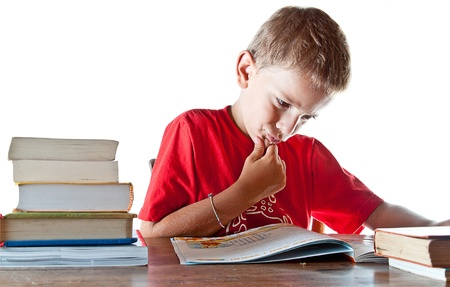 bookish: A little boy hard at work on his homework, getting ready to go back to school  Isolated on white background with plenty of copyspace