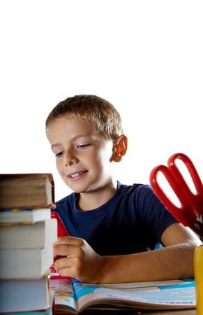 boffin: A little boy at work on his homework on his tablet computer nd a smile on his face, getting ready to go back to school  Isolated on white background with plenty of copyspace  Stock Photo