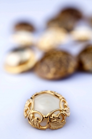 Closeup on group of vintage buttons  Focus on gold and mother-of-pearl one  photo