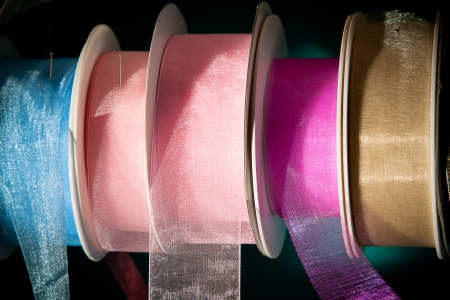 haberdashery: Colourful ribbon reels in a haberdashyery  Pink, blue and gold mesh material  Stock Photo