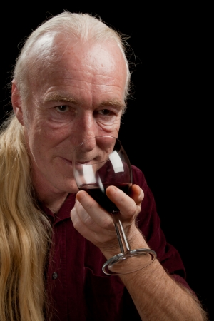 A three-quarters portrait of a man tasting wine. photo