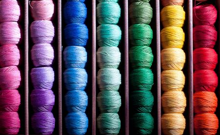 haberdashery: Close-up on colourful thread reels in a haberdashery shop arranged in a rainbow sequence. Stock Photo