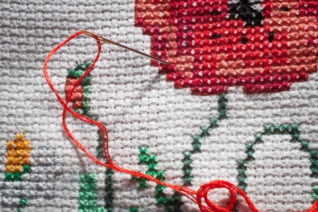 Close-up on needle and red thread  Cross-stitch embroidered tablecloth  Landscape Stock Photo - 13898968