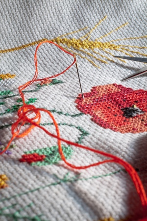 red stitches: Needle and red thread  Cross-stitch embroidered tablecloth