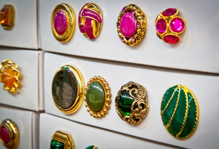 haberdashery: Boxes of jewel-like vintage buttons for sale in a haberdashery shop, pink and green  Focus on second row from right  Stock Photo