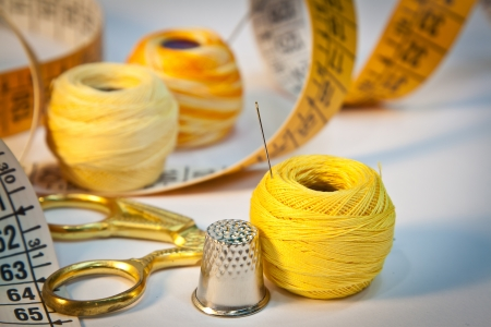 haberdashery: Close-up on sewing kit with scissors, thimble, needle, thread and tape measure