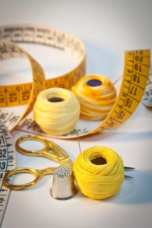 Gros plan sur kit de couture avec des ciseaux, dé à coudre, aiguilles, fil et ruban à mesurer l'orientation Portrait Banque d'images