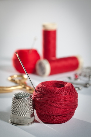 Still life with sewing theme in red, complete with thimble, thread and needle and scissors and more thread reels in the background  photo
