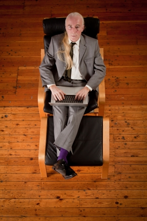 finance director: An unconventional-looking businessman working while sitting in armchair with his feet up.