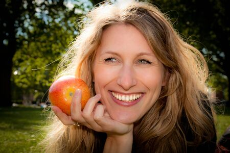 An apple a day keeps the doctor away. Beautiful young woman about to eat an apple outdoors. photo