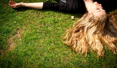 Young woman with long blond hair lying on the grass sleeping or thinking.