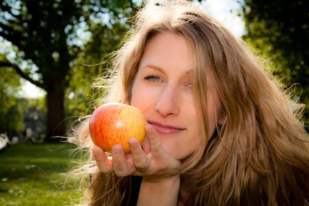 Beautiful young woman keeping healthy with her daily apple on a spring day in an urban park. photo