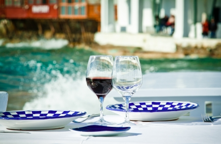 A table ready for a meal by the sea in Little Venice, Mykonos, Greece.