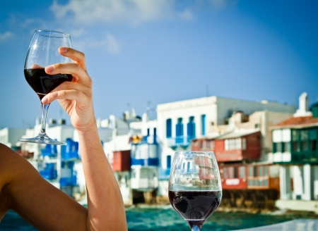 Celebrating the summer with a glass of wine in Little Venice, Mykonos, Greece.