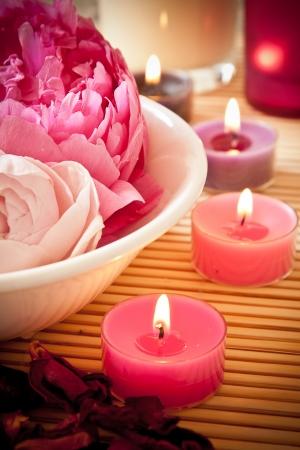 pfingstrosen: Eine Schüssel voll von schönen rosa Blüten mit Aromatherapie-Kerzen Spa-Szene
