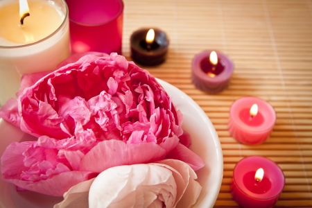 A bowl full of beautiful pink aromatherapy flowers with candles  Spa scene  Landscape orientation, focus on the flowers  photo