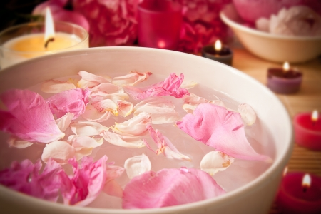 An arometherapy scene, with aromatic oils and petals in the water and candles  Focus on the petals  Spa scene  photo