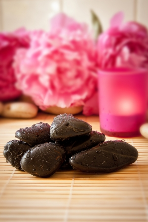 Black massage pebbles on a bamboo mat with flowers and candles in the background  Spa scene  photo