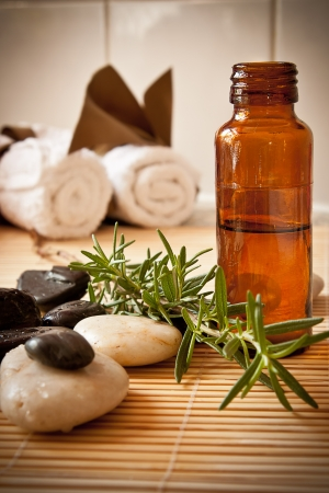 A bottle of aromatherapy oil with herbs, massage stones and towels in the background  photo