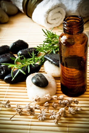 A bottle of aromatherapy oil with herbs, massage stones and towels  photo